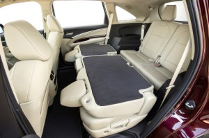 The MDX seats seven people, if two are Hobbits, and accessing the third row comes with push-button ease. Here the super-roomy middle row is folded flat; the back row folds down also. Honda photo