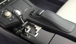 "The rotary knob (left) selects the Drive mode. ""EV Mode"" lets the ES 300h run on volts alone—briefly, slowly. ""S-D"" in the gearshift gate offers a choice between normal, sport and manual shifting. Rest your wrist on the cushion (right) to work the computer joystick and buttons just ahead of it. Note (top left) the steering-wheel heat and rear-window shade switches. Lexus"